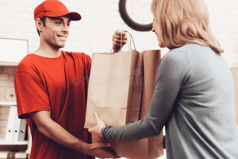 Man Arab Nationality Works in Delivery with Woman. Courier Delivery. Flowers Deliveryman. Worker Man Arab Nationality. White Interior. Deliveryman Arab royalty free stock photo