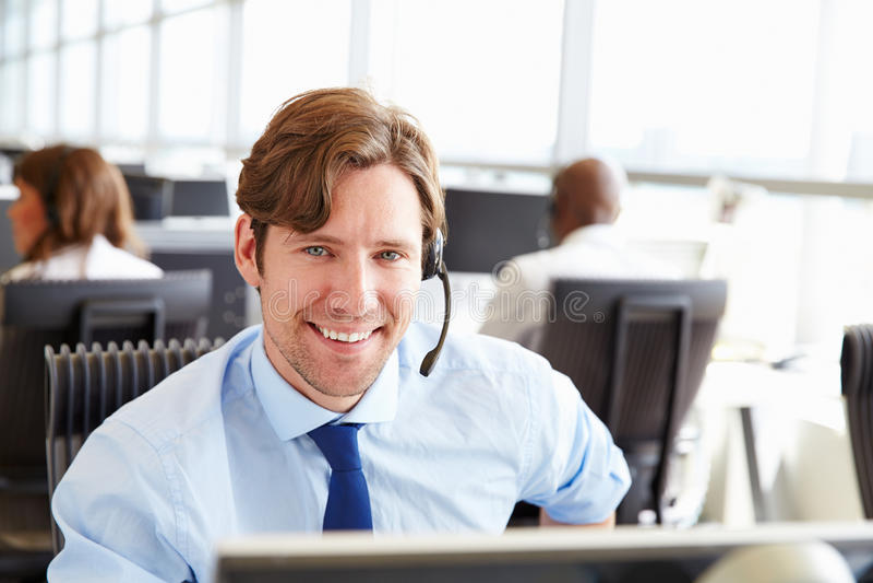 Man arbete i en call center som ser till kameran, närbilden arkivbild