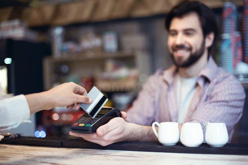 Man arbete i en coffee shop som tar betalning vid kreditkorten från arkivfoton
