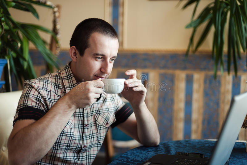 Man arbete i ett kafé på en bärbar dator royaltyfria foton