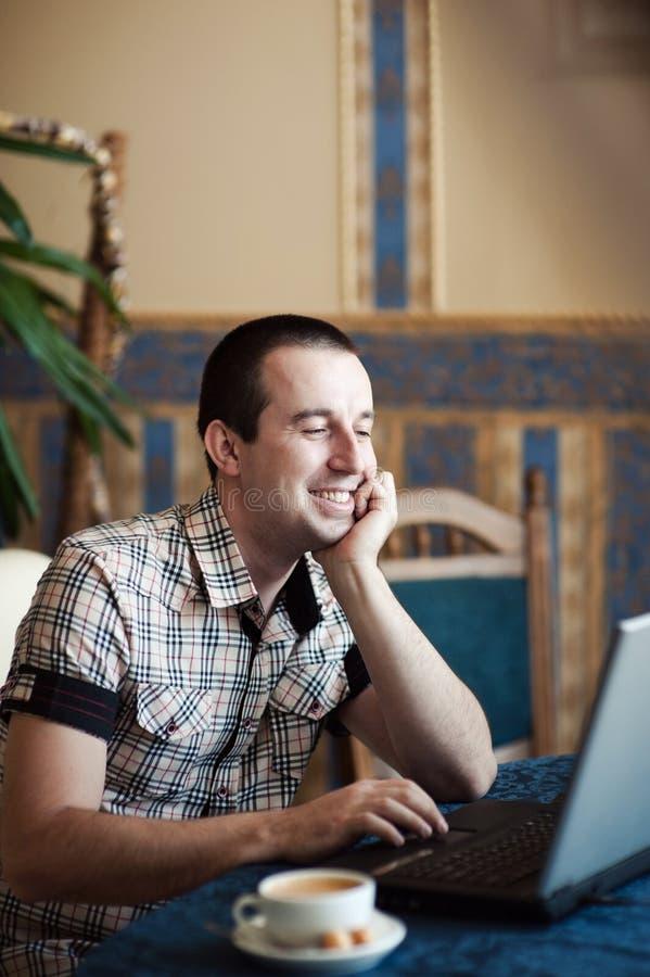 Man arbete i ett kafé på en bärbar dator royaltyfri bild