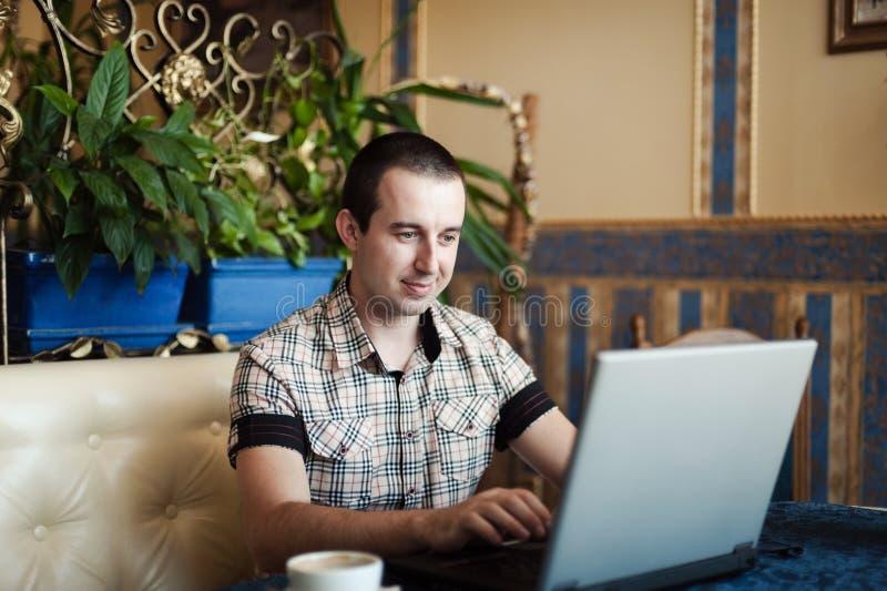 Man arbete i ett kafé på en bärbar dator royaltyfria bilder