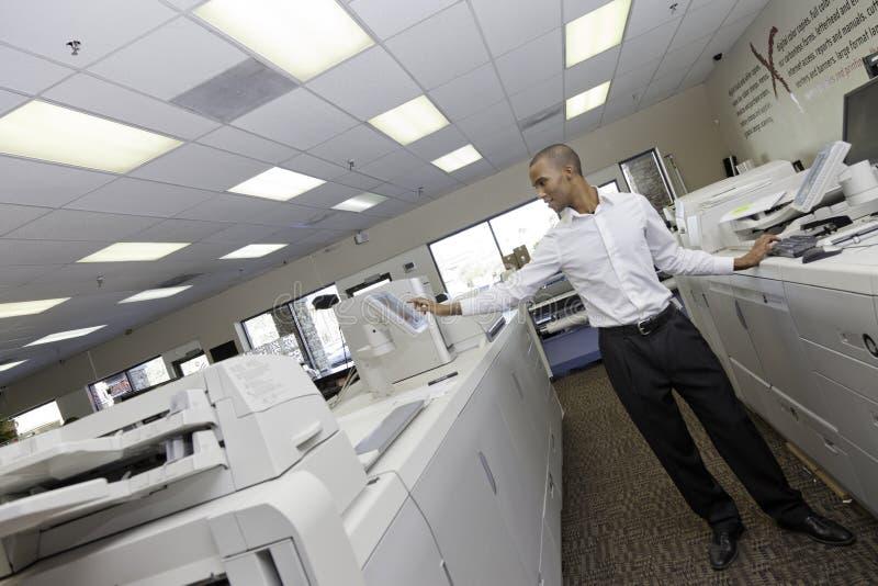 Man arbete i tryckpress mellan maskinen för två kassaapparat royaltyfri bild