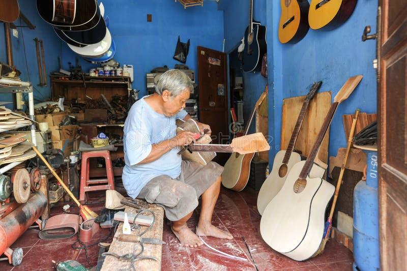 Man arbete på byggande av en hand - gjord gitarr på Yogyakarta royaltyfri fotografi