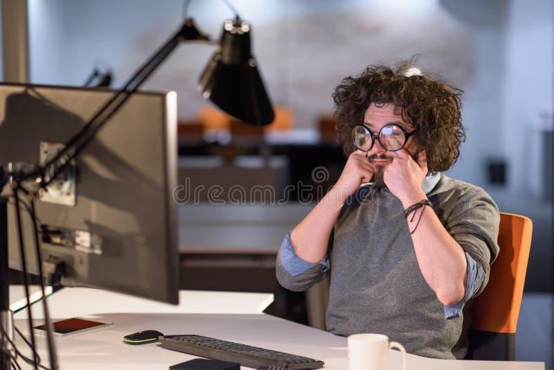 Man arbete på datoren i mörkt startup kontor arkivfoto
