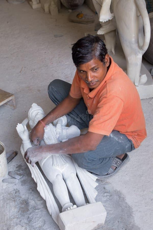 Man arbete på en staty på ett seminarium i Delhi, Indien arkivfoto