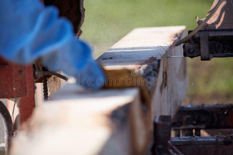 Man arbete på ett bärbart sågmalningbråte royaltyfri foto