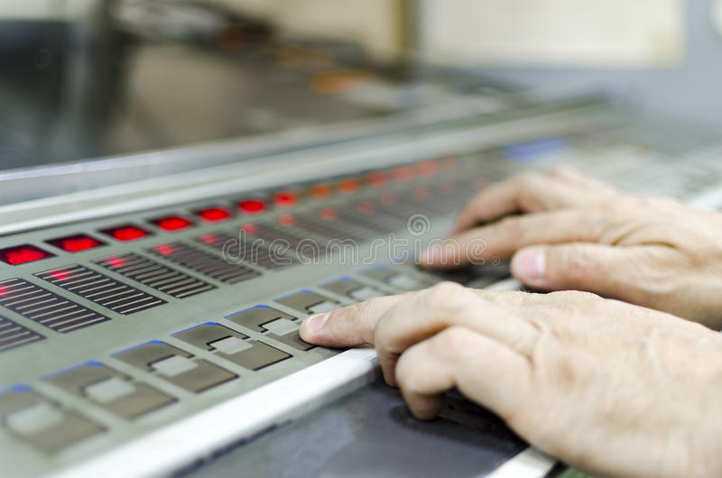 Man arbete på printingmaskinen i tryckfabrik arkivbild