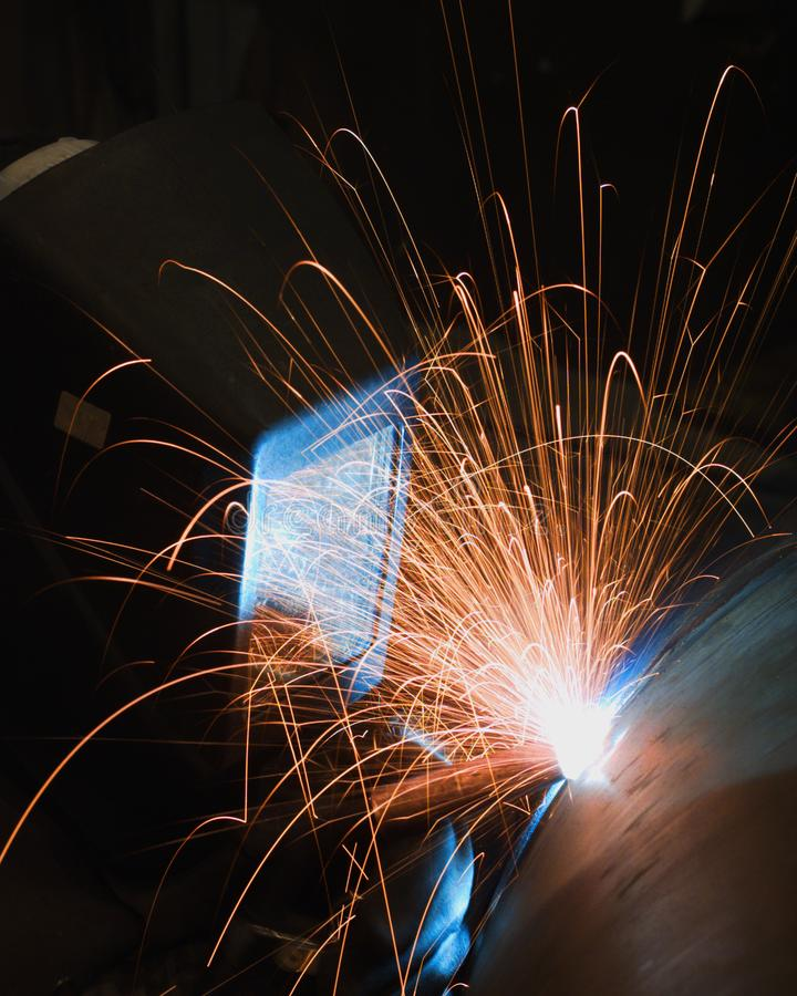 A professional welder, welding the top on a pressure vessel stock photography
