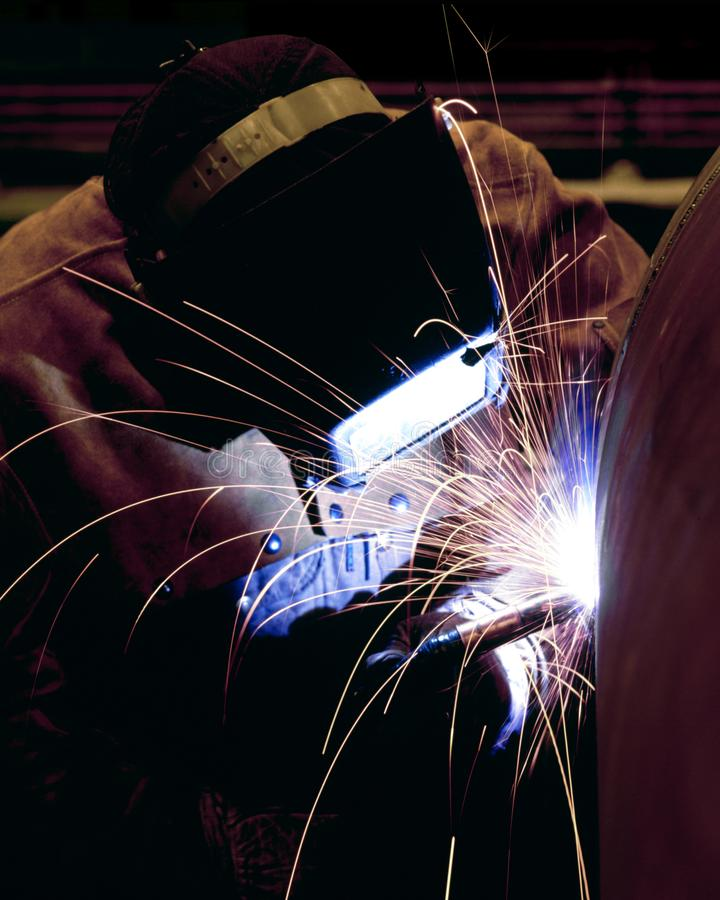 A professional welder, welding the top on a pressure vessel royalty free stock image