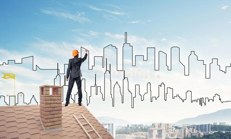 Man architect draw silhouette of modern city on blue sky. Mixed. Engineer man standing with back on house roof and drawing city. Mixed media royalty free stock photos