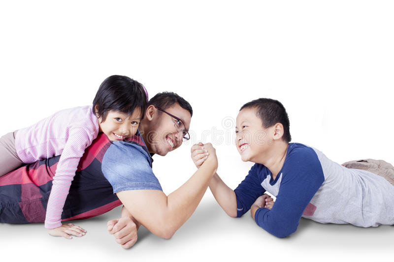 Man arm wrestling with his son. Portrait of young father playing with his children and arm wrestling with his son, isolated on white royalty free stock image