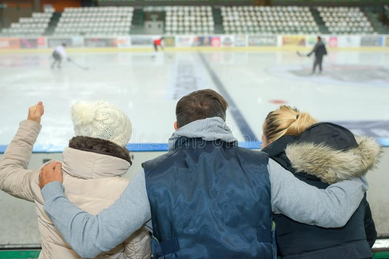 Man with arms around two women watching ice hockey game. Ice stock photos