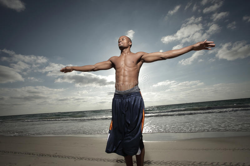 Man with arms outstretched. Man on the beach with his arms outstretched with the sun behind him royalty free stock photography