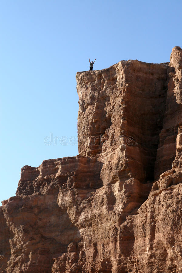 Man with arms raised to the top of the mountain stock image