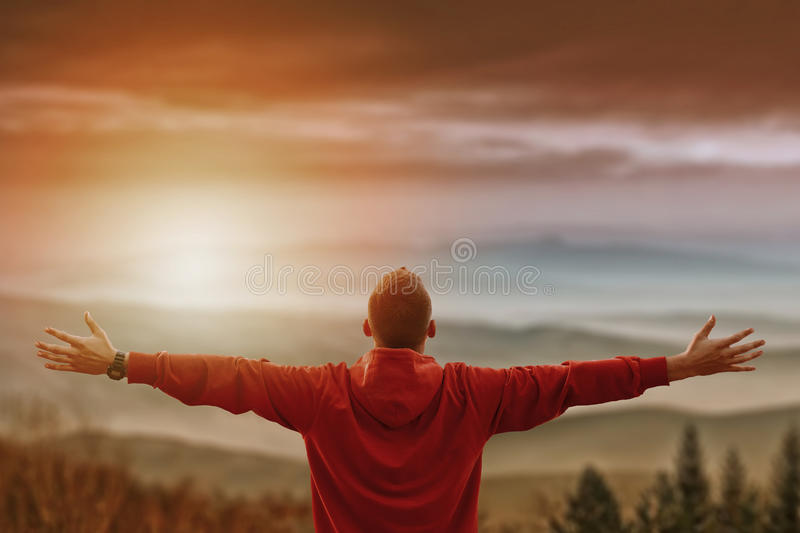 Man with arms spread looking at mountains. Vivid photo with layered mountains valley in front. Man has his back facing the camera with mountains in background royalty free stock photo