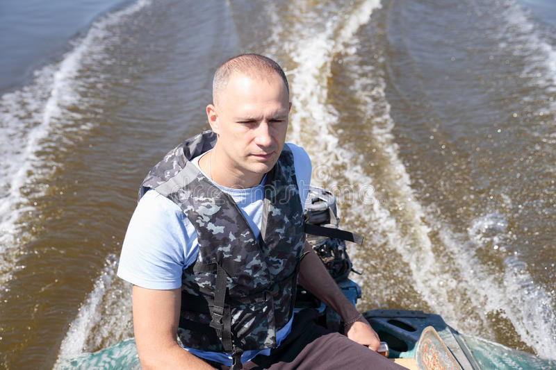Man in army fatigues moving boat. Man in army fatigues moved by motor boat royalty free stock photos