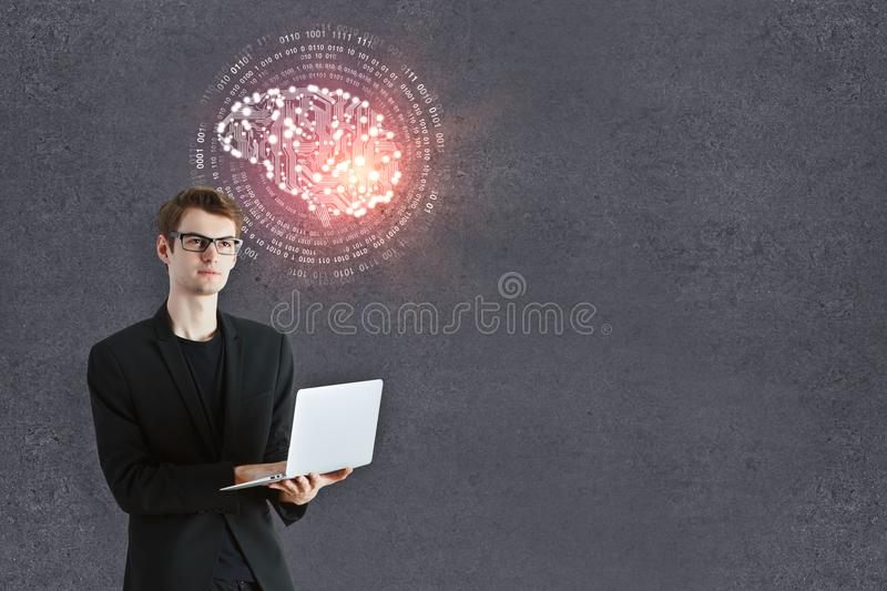 Man with artificial brain. Thoughtful young businessman with laptop and abstract circuit brain standing on concrete wall background with copy space. Artificial stock photos
