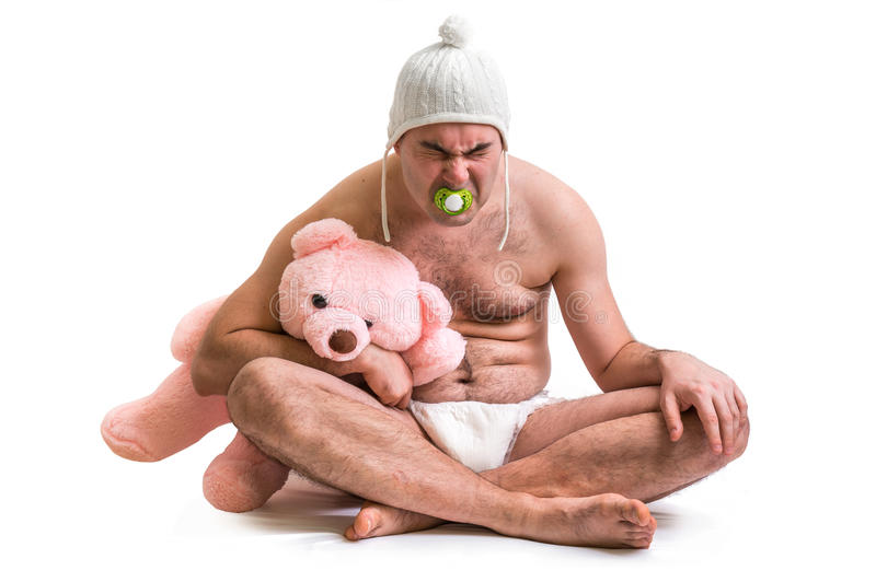 Man as baby. Child in diaper with pink teddy bear. royalty free stock photography
