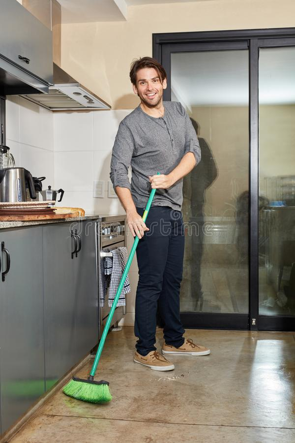 Man as a houseman during spring cleaning in the kitchen stock photo