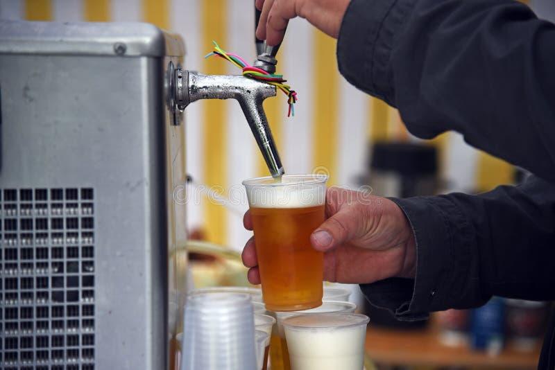 Man& x27; as mãos de s em uma cerveja batem a cerveja de derramamento em vidros plásticos no A M. imagens de stock royalty free