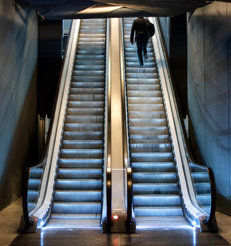 Man ascending an escalator from a subway. Riding up the moving treads towards daylight at the top, view from the bottom stock photos
