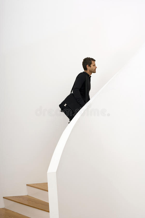Man ascending staircase, carrying shoulder bag, profile royalty free stock image