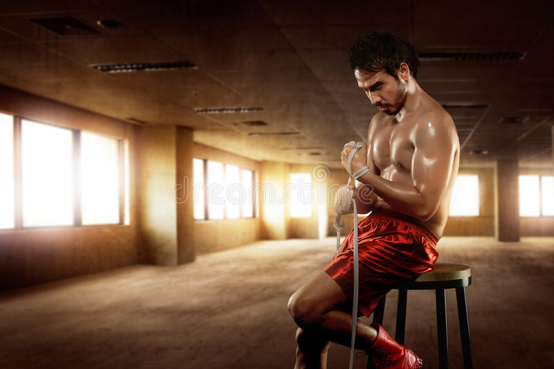 Man asian boxer sitting with wearing white strap. On wrist in the gym stock photo