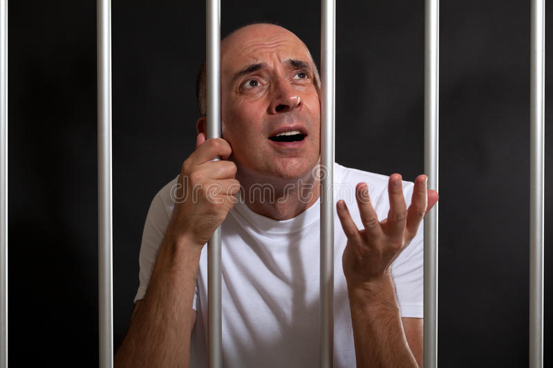 Man asking for mercy in prison. Behind bars stock image