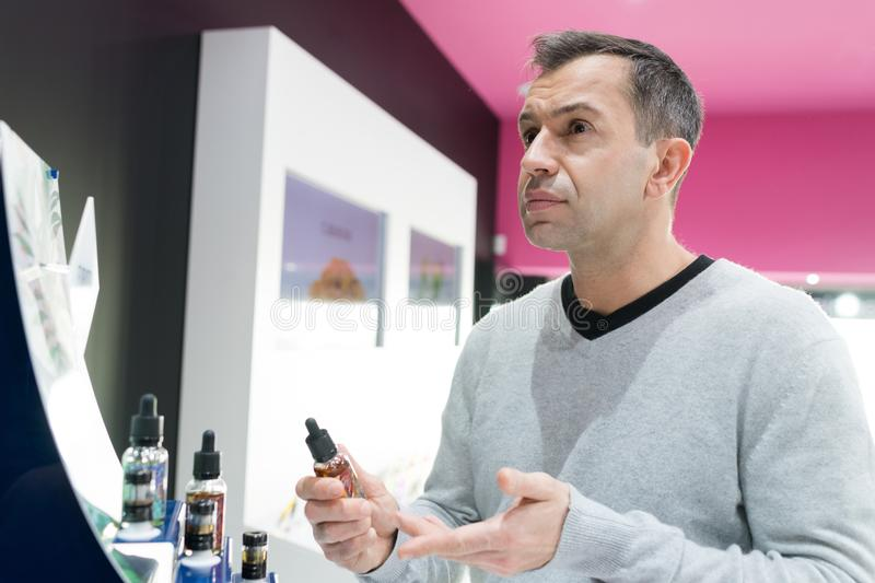Man asking for refund in e-cigarette shop. Man asking for a refund in an e-cigarette shop stock image