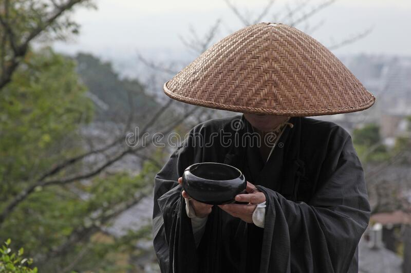 Man asks for alms. Hiding his face stock photography