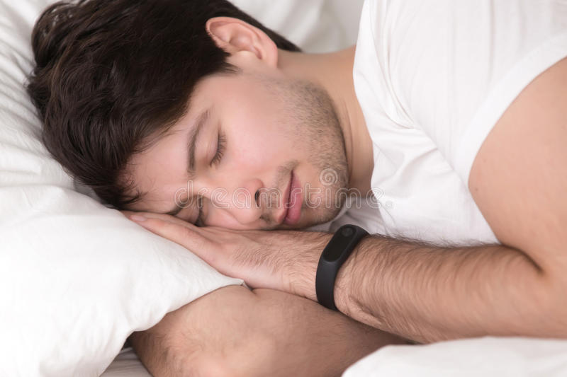 Man asleep in bed wearing smart wristband for sleep tracking royalty free stock photo