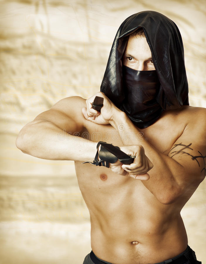 Man assassin with torso in mask. Man assassin with torso in black mask and hood holding two knifes in hands royalty free stock image