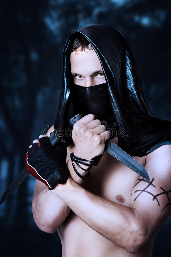 Man assassin with torso in mask. Man assassin with torso in black mask and hood holding two knifes in hands royalty free stock photo