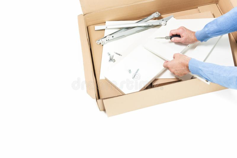 Man assembles flat packed furniture isolated royalty free stock images