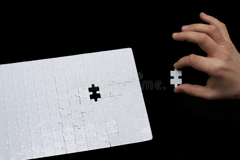 A man assembles puzzle piece on black background royalty free stock image