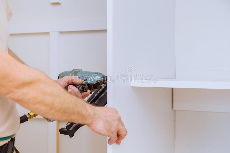 Man assembling the closet with wooden shelves royalty free stock image