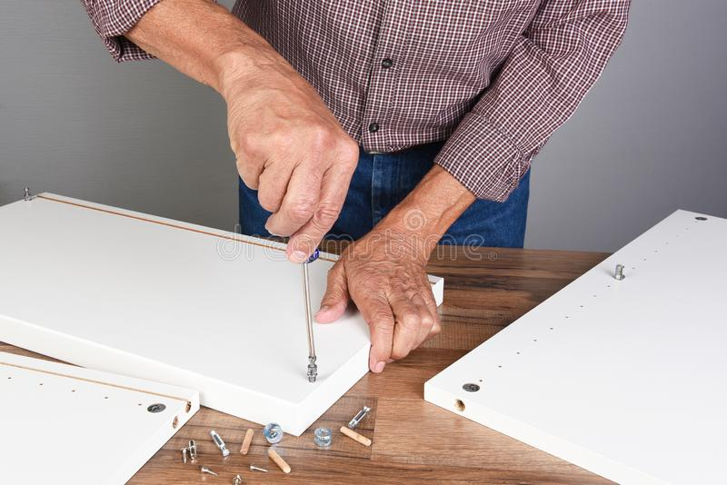 A man assembling a DIY piece of furniture. Person is using a screwdriver inserting a piece of hardware.  royalty free stock image