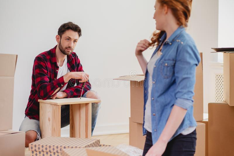 Man assembling furniture while furnishing new home after relocation with wife royalty free stock photos