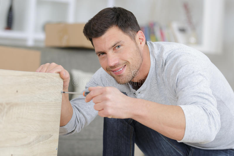 Man assembling furniture at home on floor royalty free stock photography