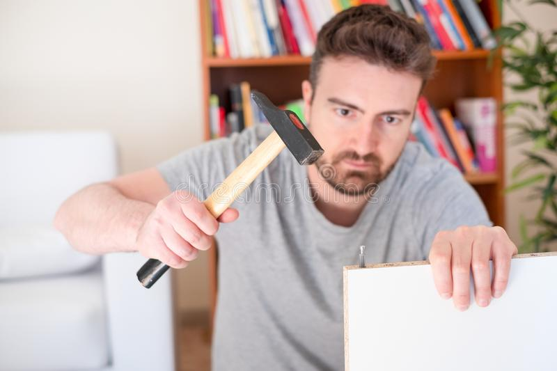 Man assembling furniture at home on the floor stock image