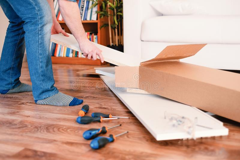 New home and man assembling furniture do it yourself stock photo