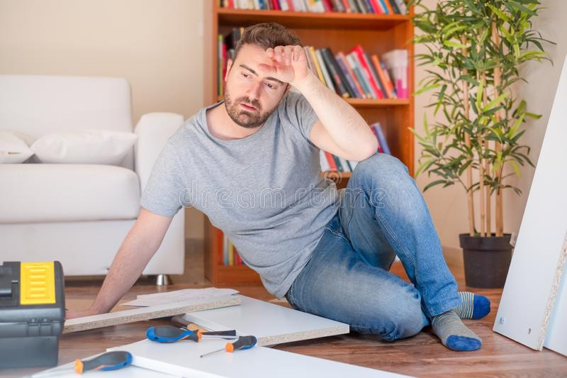 Man assembling furniture at home on the floor stock photo