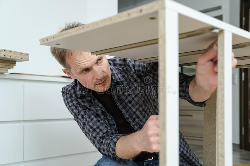 The man is assembling the furniture at home royalty free stock photos