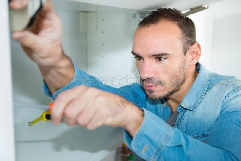 Man assembling kitchen cupboard. Man assembling a kitchen cupboard stock photography