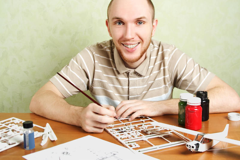 Man assembling plastic airplane model. And painting pieces, smiling, looking at camera stock photos