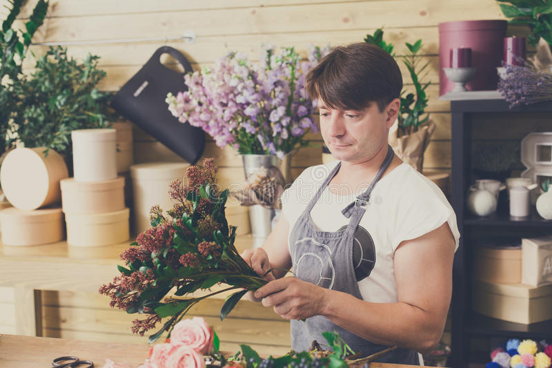 Man assistant in flower shop delivery make bouquet royalty free stock image
