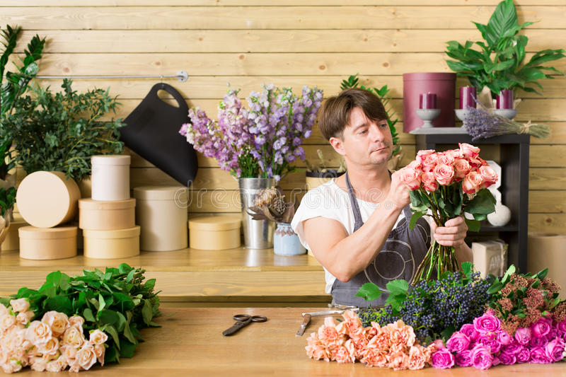 Man assistant in flower shop delivery make rose bouquet royalty free stock image