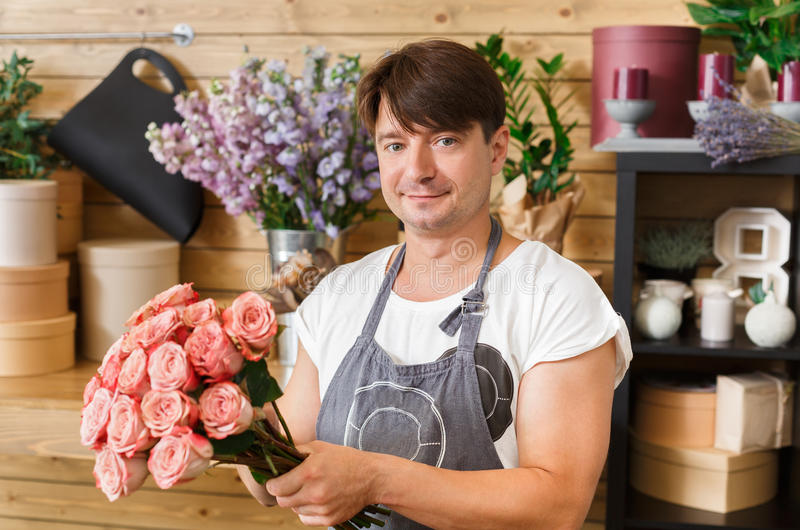 Man assistant in flower shop delivery make rose bouquet royalty free stock photography