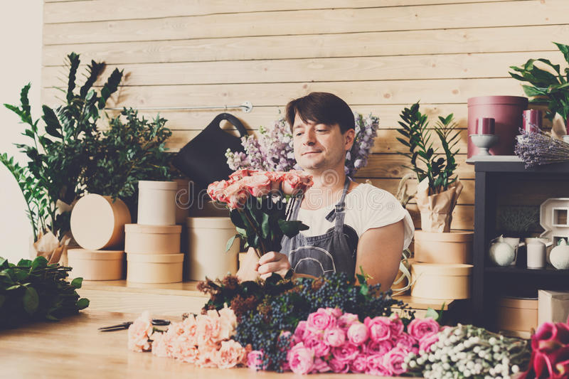 Man assistant in flower shop delivery make rose bouquet stock photo